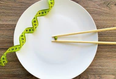 Imagem de um prato de porcelana na cor branca. Sobre ele um grão de ervilha, um hashi e uma fita métrica.