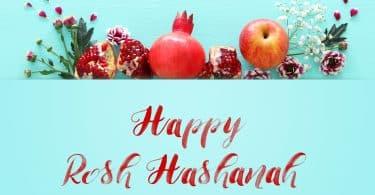 Imagem de várias frutas como romã e maçã decoradas com ramos de flores para compor os rituais para celebrar o ano novo judaíco. À frente dos elementos está escrito em inglês a frase: Happy Rosh HaShaná.