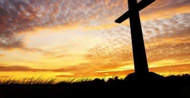 Imagem de uma cruz com o pôr do sol ao fundo