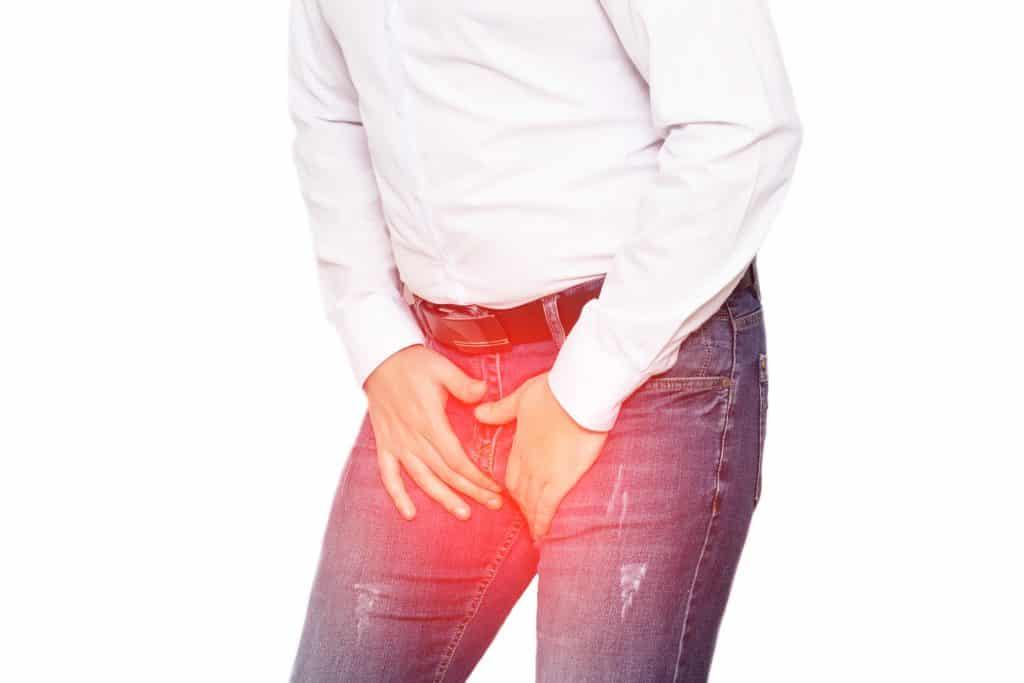 Imagem de um homem usando camisa branca e calça jeans. Ele está com as mãos sobre a calça, próximo ao seu órgão genital. Ele foi diagnosticado com uma infecção denominada candidíase masculina.