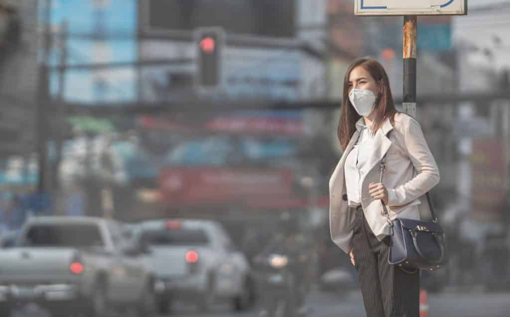 Mulher usando máscara parada no farol