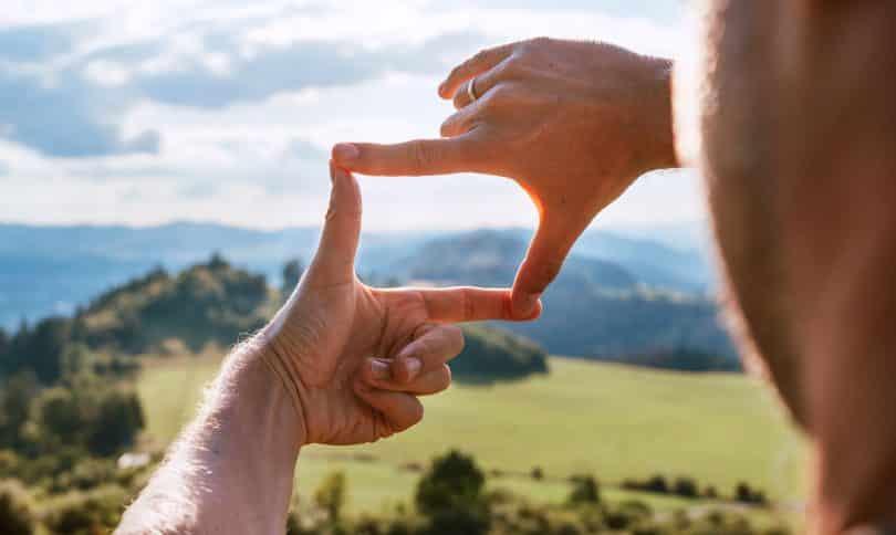 Homem vendo a paisagem através do ângulo formado pelas suas mãos