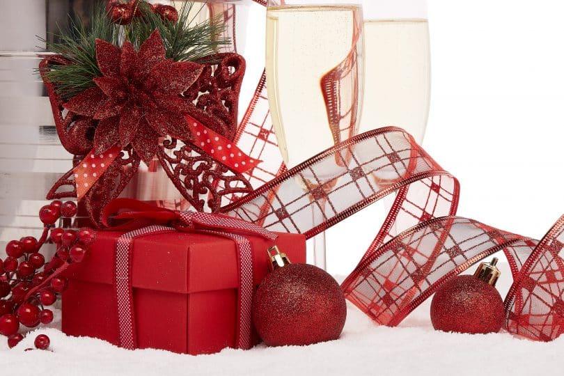Imagem de uma mesa decorada com vários itens para celebrar o natal e o ano novo. Entre eles, descatam-se: uma caixa de presentes na cor vermelha, laçcos de fita com flores vermelhras, bolas de natal e duas taças de champanhe.