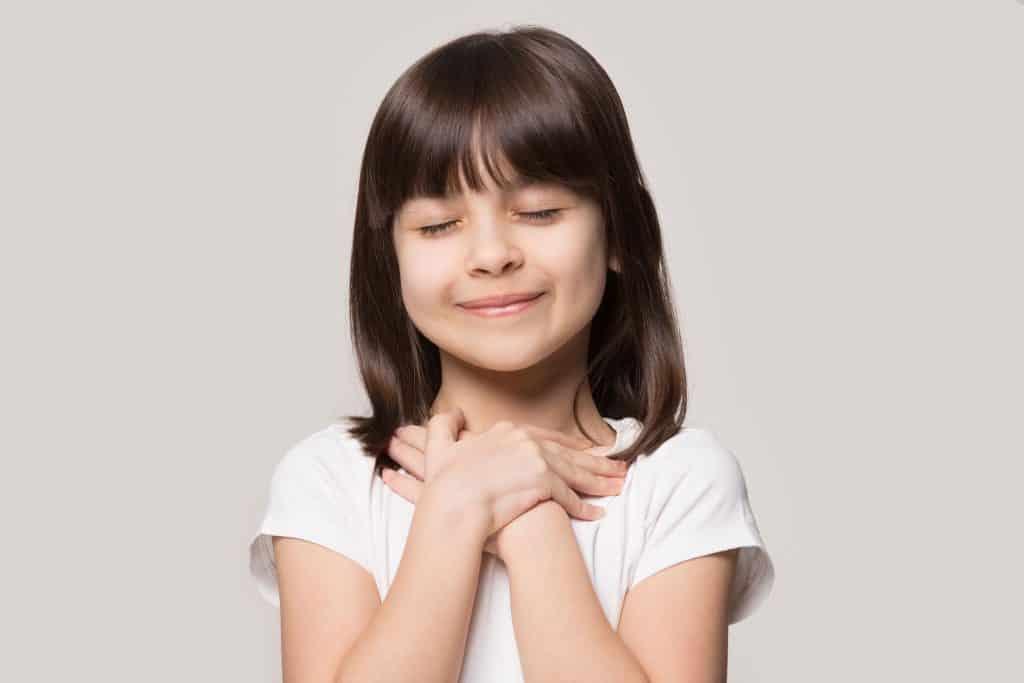 Menina com as mãos no peito representando a gratidão com uma blusa branca no fundo cinza