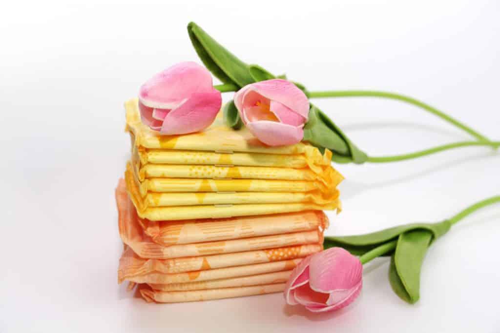 Image de vários absorventes embalados e empilhados e sobre eles botões de rosa na cor rosa.