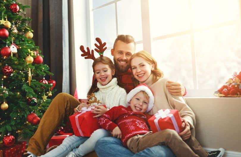 Uma família sentada no sofá enquanto abrem presentes de Natal