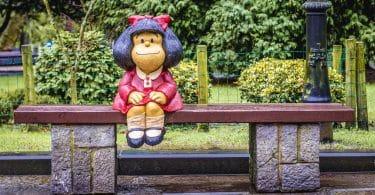 Estátua da personagem Mafalda criada por Pablo Irrgang. Ela está sobre um banco em um parque de Oviedo, na Espanha.
