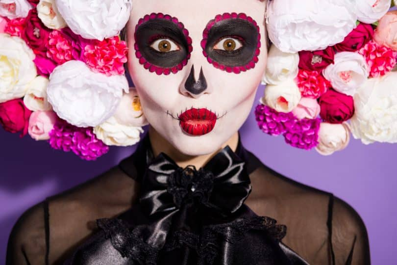 Imagem do rosto da La Catrina - Deusa da Morte. Sobre a sua cabeça uma tiara repleta de flores nas cores branca, rosa e roxa. Ela usa uma blusa de seda preta com um laço na gola. Seus olhos estão pintatos de preto e roxo.