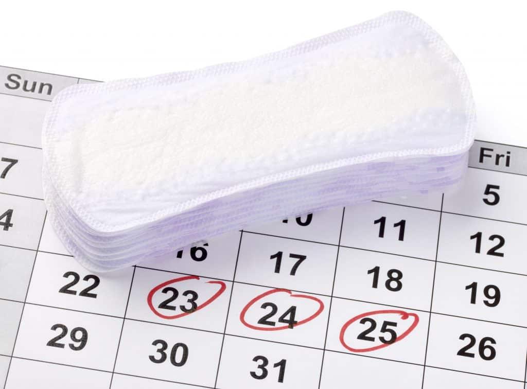 Imagem de um calendário onde os dias 23, 24 e 25 estão circulados de caneta vermelha. Ele representa o ciclo menstrual. Sobre ele, vários absorventes sem uso.