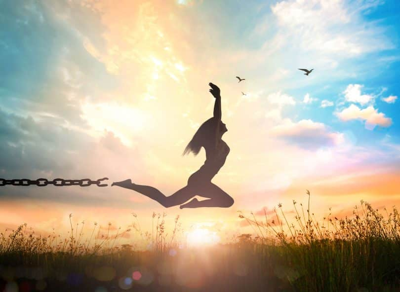 Silhueta de mulher pulando num campo, se livrando de uma corrente no tornozelo.