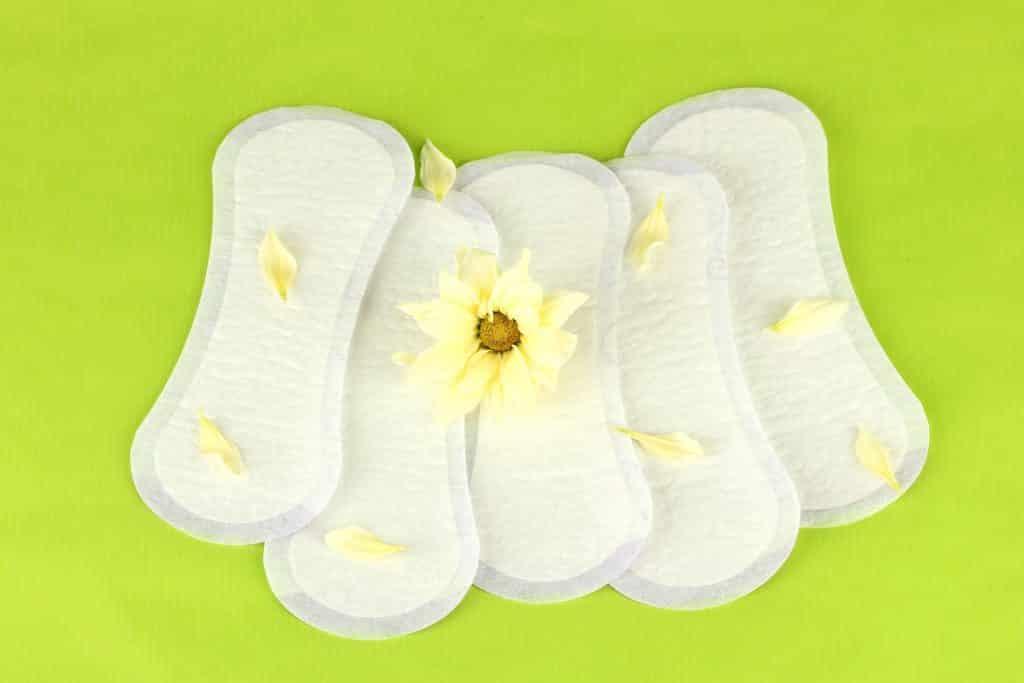 Imagem de vários absorventes femininos sem uso, eles estão abertos e sobre eles pétalas de margarida e ao centro um margarida amarela.