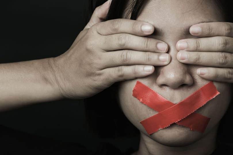 Mulher branca com os olhos tapados por par de mãos e fitas vermelhas sobre a boca.