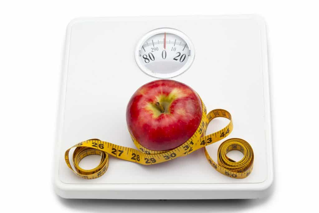 Imagem de uma balança corporal de banheiro e sobre ela uma linda e saborosa maçã vermelha enrolada em uma fita métrica.