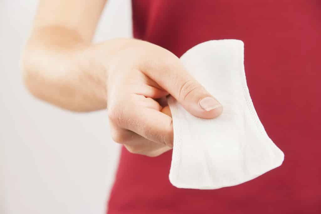 Imagem de uma mulher usando uma camiseta vermelha. Em uma das mãos ela segura um absorvente.