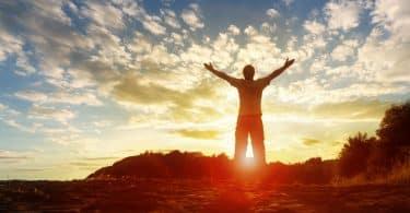 Homem com as mãos levantadas em sentido ao pôr do sol