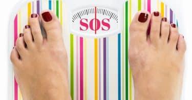 Imagem de uma balança de peso de banheiro colorida e no visor dos números está escrito a palavra SOS em cor rosa. Sobre a balança os pés de uma mulher com as unhas pintadas de vermelho escuro.