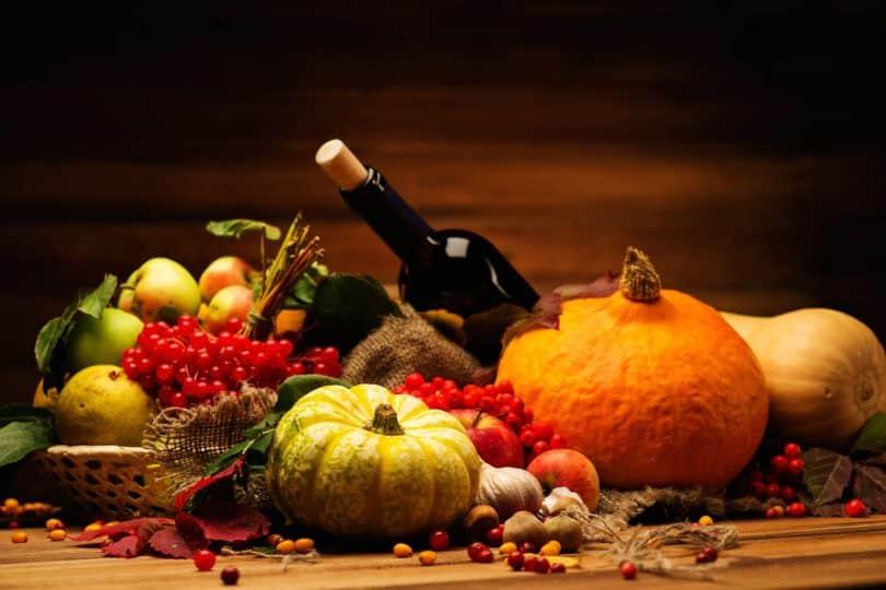 Mesa com garrafa de vinho e repleta de frutas.