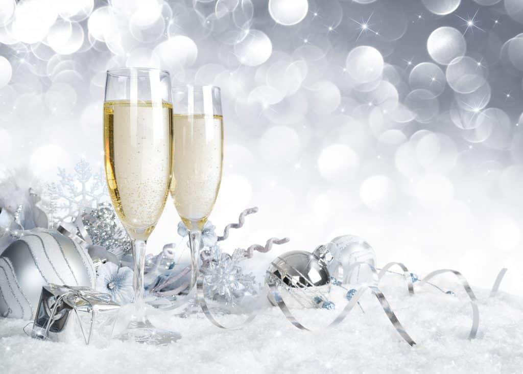 Imagem de uma mesa decorada com bolas e serpentinas na cor prata para celebrar a chegada do ano novo. Sobre a mesa, duas lindas taças de champanhe.
