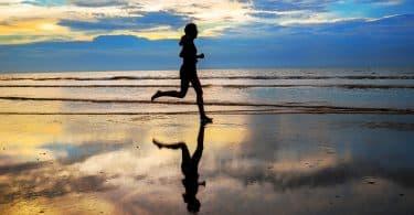 Silhueta feminina correndo à beira do mar.