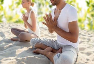 casal fazendo exercícios de ioga sentado ao ar livre