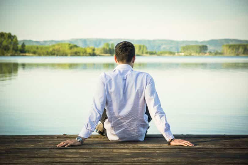 Homem sentado de costas em ponte com rio e árvores ao fundo