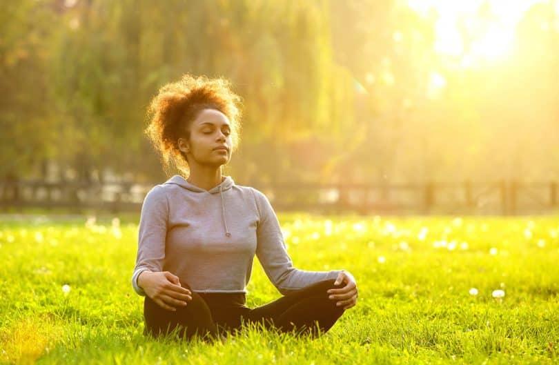 Com os olhos fechados, mulher sentada na grama medita.