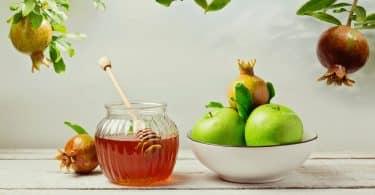 Imagem de uma mesa de madeira na cor branca e sobre ela uma tigela com maças verdes e romã, um pote com mel e uma romã ao lado do pote. Esses são alguns alimentos para celebrar o ano novo judaíco.