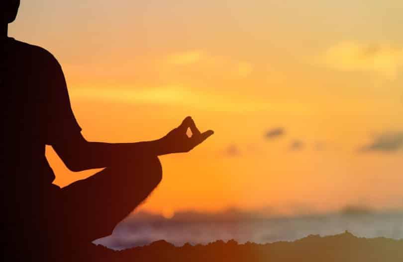 Silhueta de uma pessoa meditando.