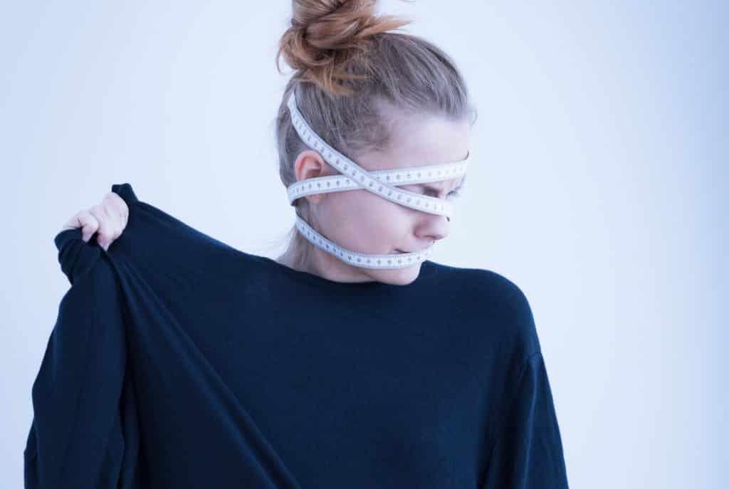 Imagem de uma mulher usando uma blusa de manga longa preta. Ela sofre de anorexia e está com uma fita métrica enrolada em sua cabeça.