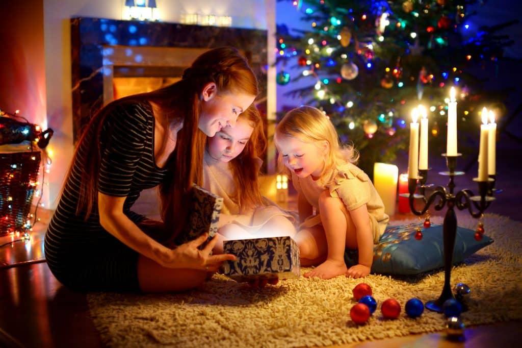Uma mulher e duas crianças pequenas abrindo um presente de Natal perto de uma árvore de Natal