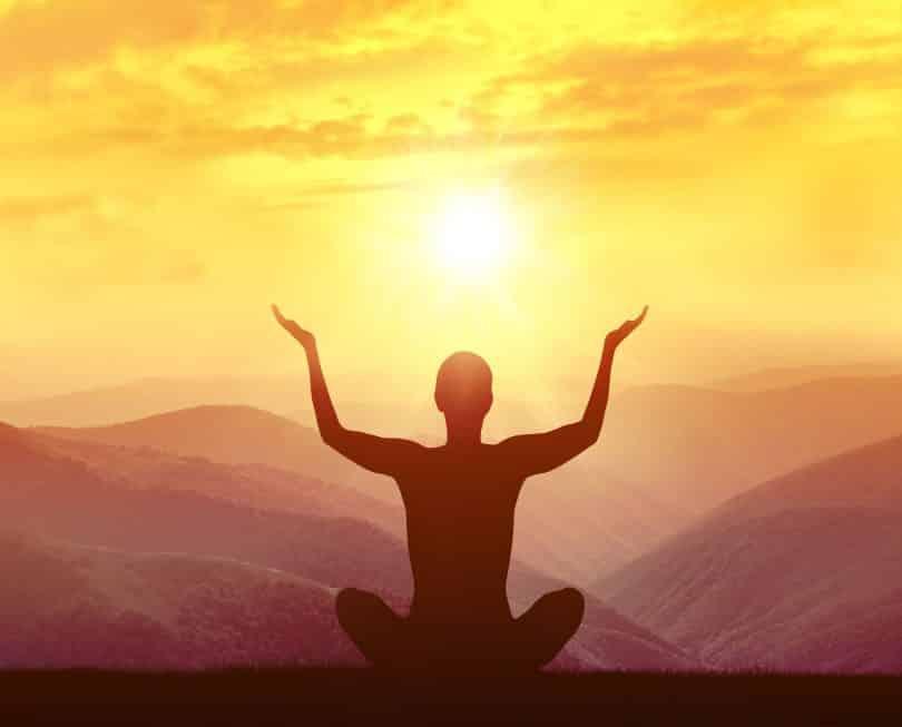 Silhueta de uma mulher praticando ioga nas montanhas ao nascer do sol.