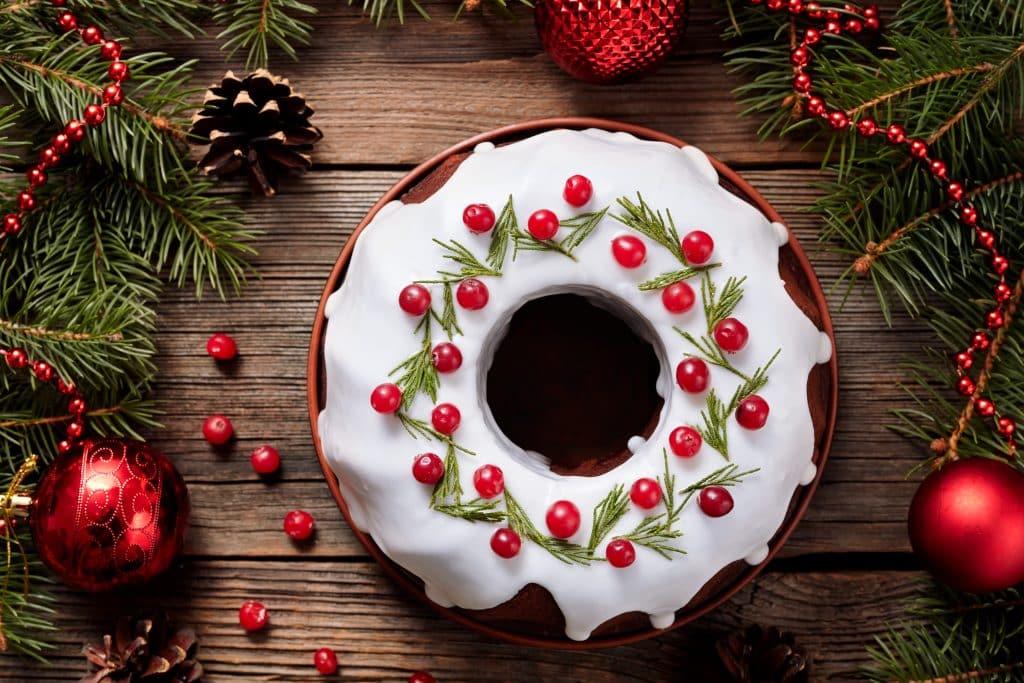 Imagem de um lindo e delicioso bolo de natal, coberto com glacê, decorado com cerejas e ramos verdes. O bolo está disposto sobre uma mesa de madeira, decorada com bolas vermelhas de natal.