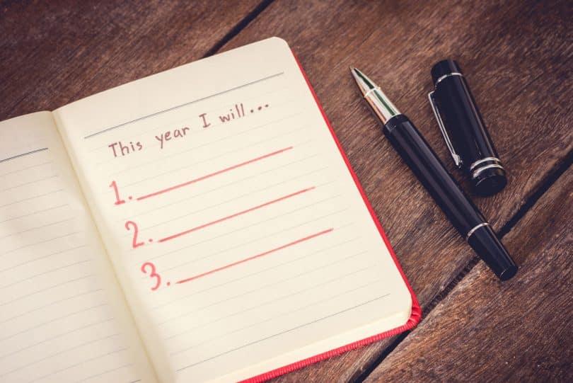 Caderno de anotações com canetas pretas ao lado.