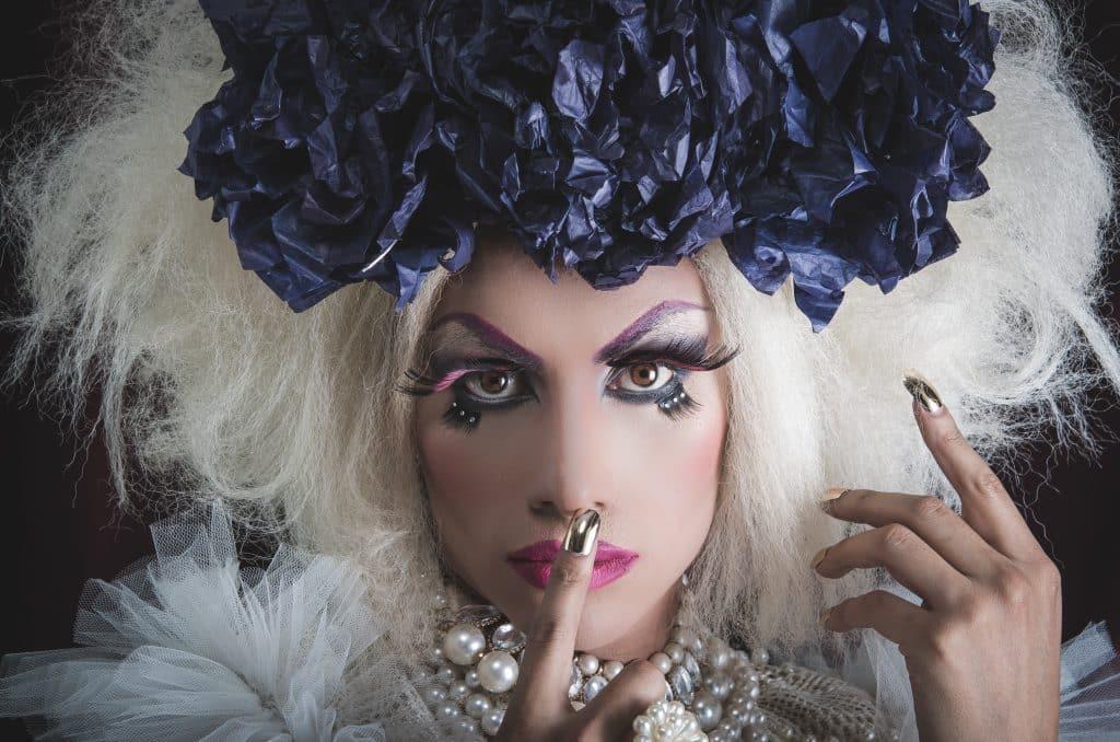 Imagem de um belo travesti, usando uma linda maquiagem e um arrnajo azul sobre a peruca de cabelos loiros. Suas unhas estão pintadas de dourado e usa  um lindo colar de pérolas.