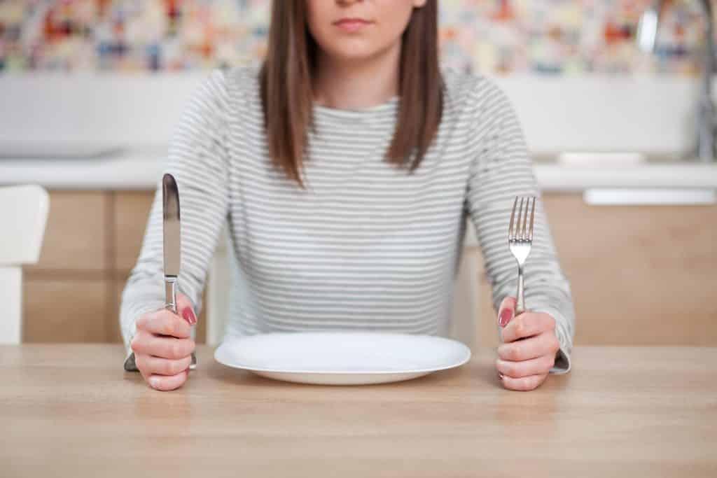 Imagem de uma moça usando uma blusa com listras branca e cinza de manga longa sentada à frente de um prato vazio. Em suas mãos ela segura um garfo e uma faca.
