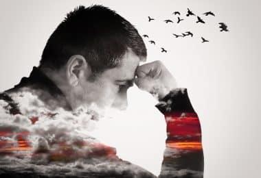 Imagem de um homem pensando com o punho erguido na testa. Nuvens cobrem seu peito e braços enquanto pássaros voam de sua cabeça.