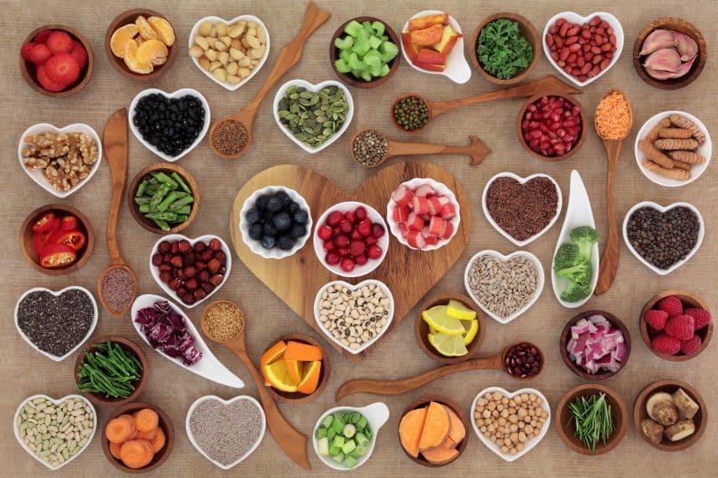 Diversos alimentos em tigelas dispostos sobre mesa de madeira.