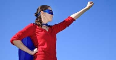 Mulher vestida como super-heroína ergue um dos braços enquanto repousa o outro na cintura.