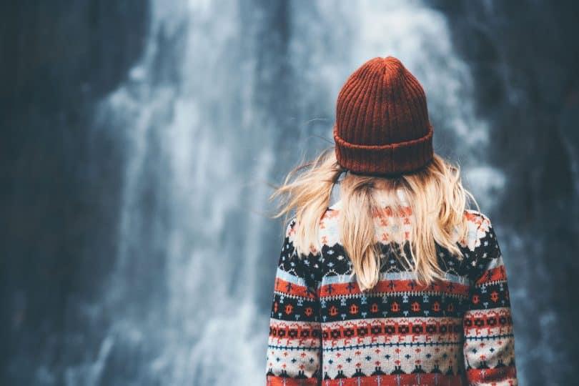 Mulher branca e loira de costas para uma cachoeira.