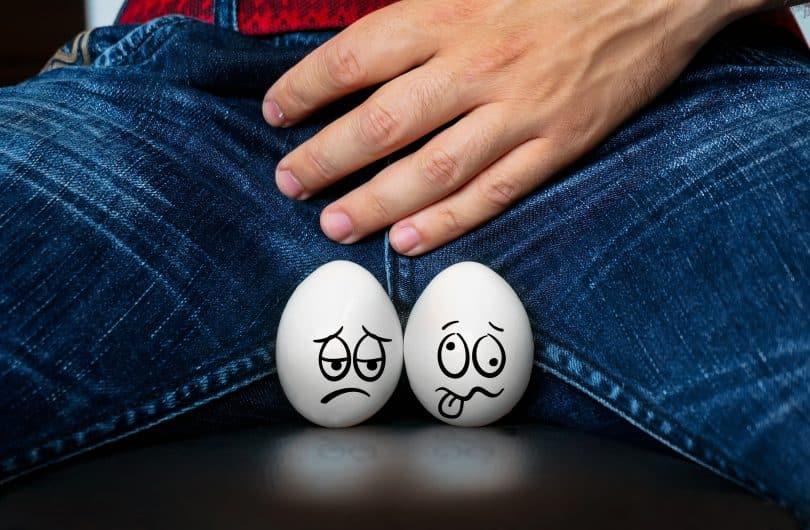 Imagem de um homem sentado. Ele usa calça jeans e está com uma das mãos sobre o seu órgão genital. Ele foi diagnosticado com candidíase masculina. Ele está com uma infecção.