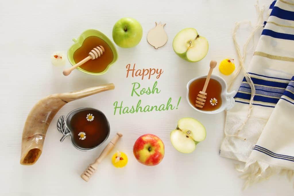 Imagem de vários elementos como maçãs, mel, dosador, que compõem a celebração do ano novo judaíco. No centro desses elementos está escrito a palavra: Happy Rosh HaShaná em inglês.