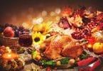 Imagem de uma linda mesa composta por vários tipos de comidas para celebrar o Natal. Temos: peru assado, frutas variadas, castanhas e vinho.