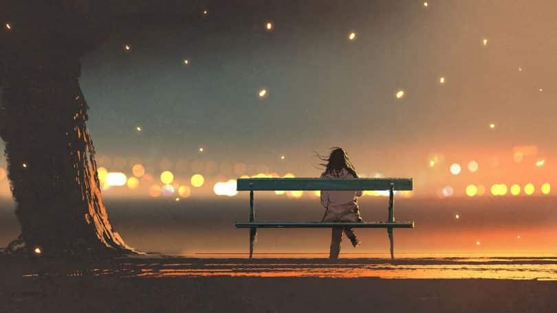 Mulher sentada num banco durante a noite.