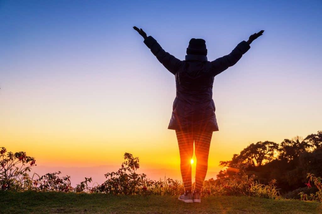 Mulher com os braços estendidos orando com raios de sol na colina.