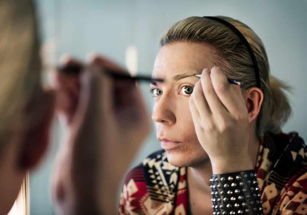Imagem de um travesti se maquiando em frente ao espelho.