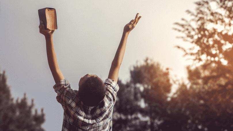 Homem segurando uma bíblia erguendo os braços pra cima