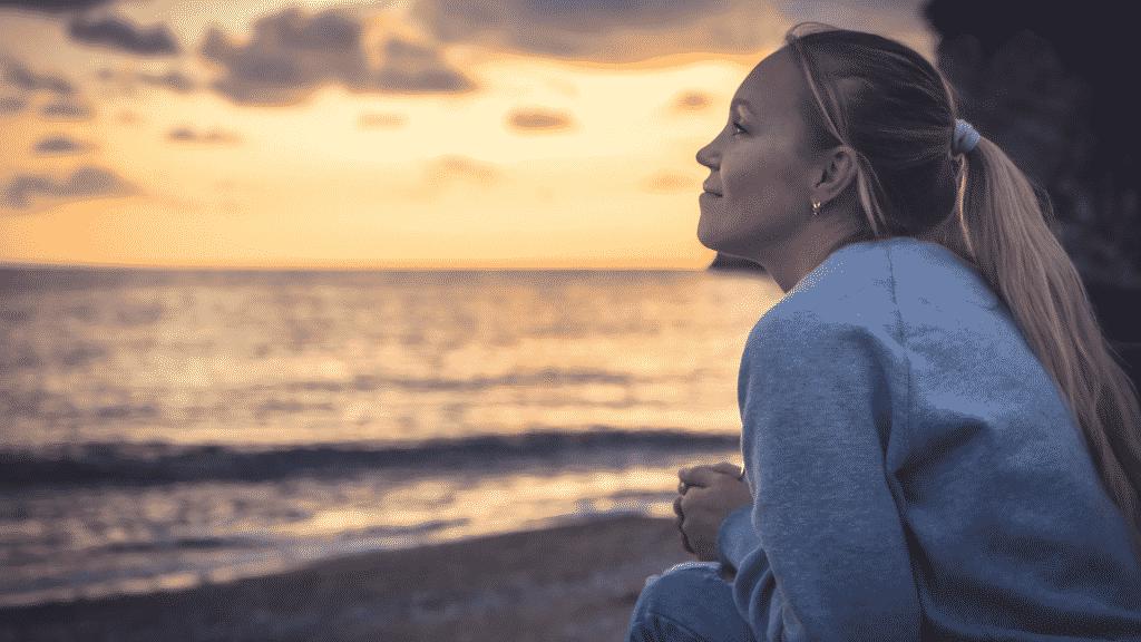 Mulher na beira do mar olhando o horizonte