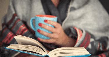 Mulher lendo um livro enquanto segura uma xícara de café