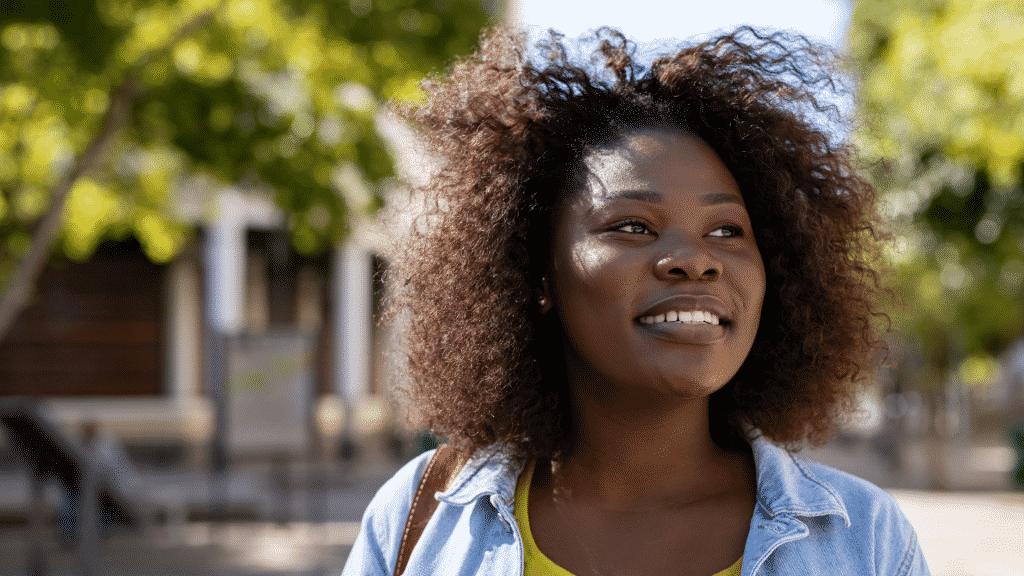Mulher negra sorrindo enquanto caminha na rua