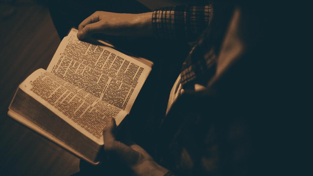 Homem sentado e lendo a bíblia
